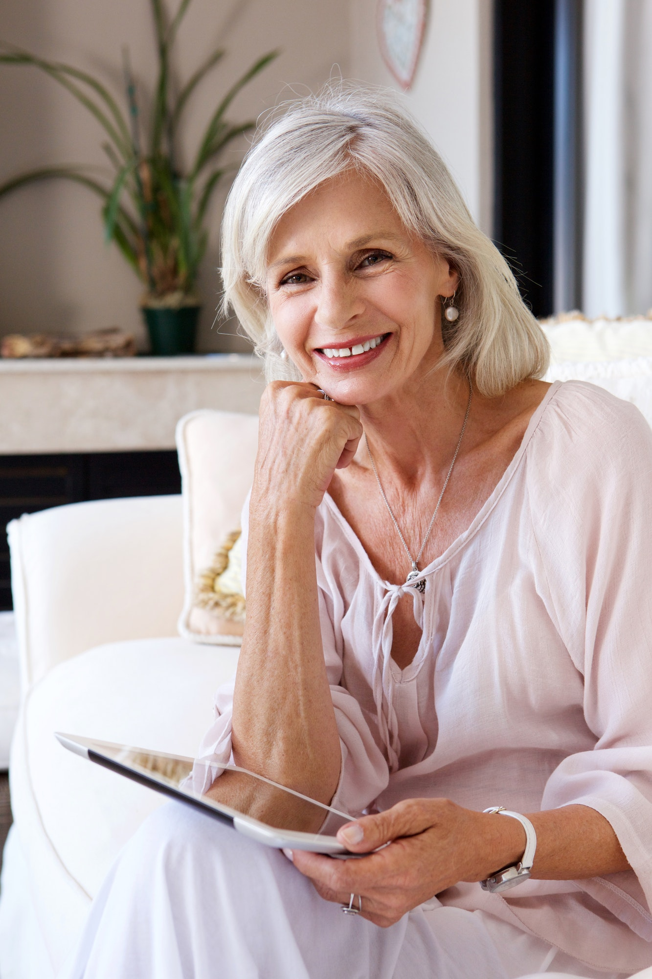 smiling older woman in living room with tablet